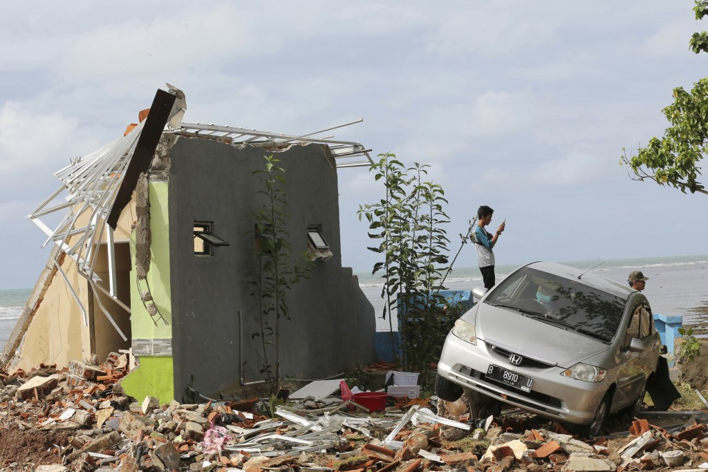 A man takes a photo with his mobile phone at a cottage damaged by a tsunami in Carita beach, Indonesia, Monday, Dec. 24, 2018. Doctors worked to save ...