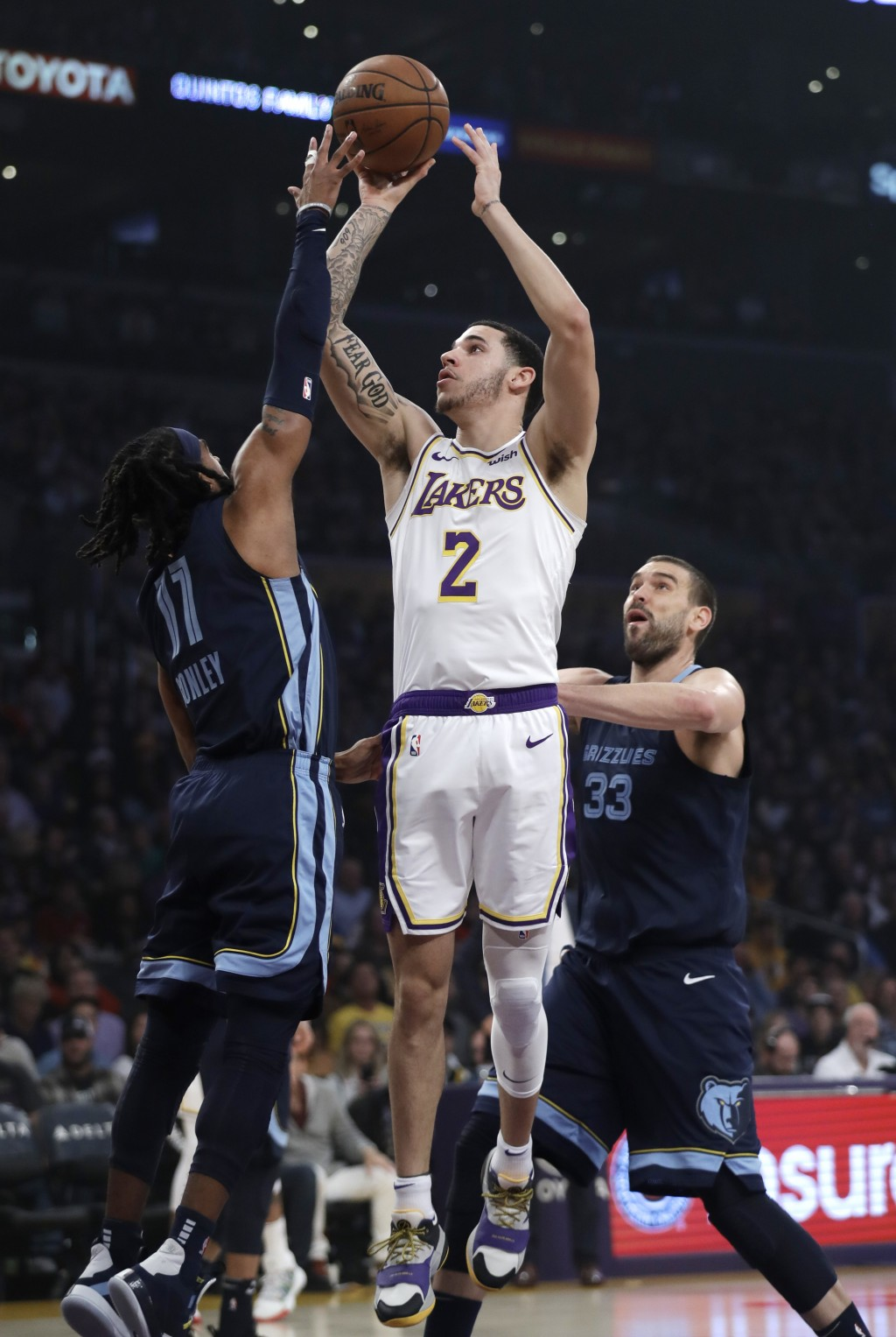 Los Angeles Lakers' Lonzo Ball (2) shoots over Memphis Grizzlies' Mike Conley, left, and Marc Gasol during the first half of an NBA basketball game Su...