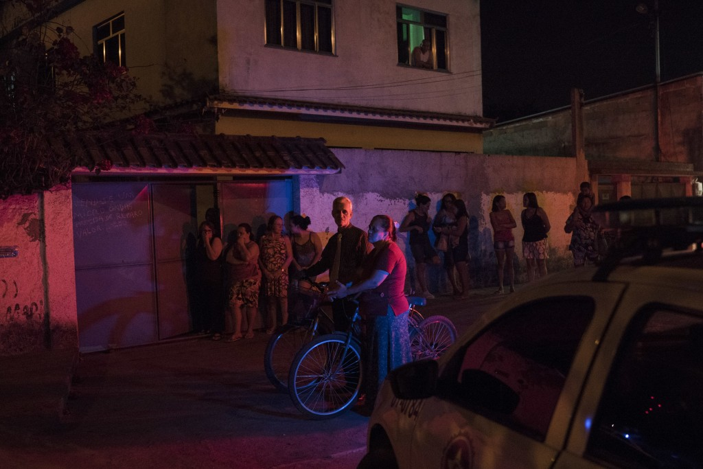 In this Aug. 31, 2018 photo, residents watch police work a crime scene where the body of a man was found on the floor of a kiosk in Duque de Caxias, g...