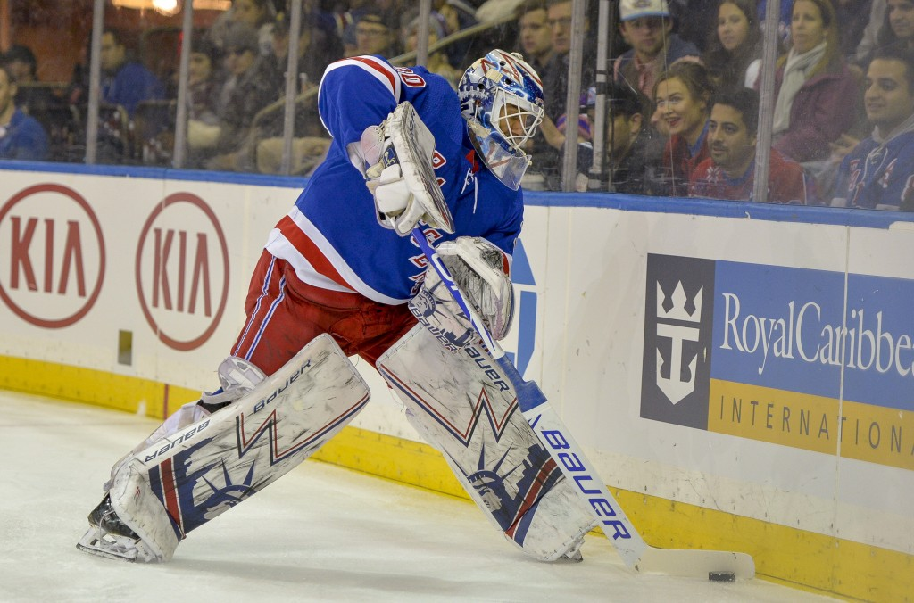 New York Rangers goaltender Henrik Lundqvist (30) goes behind the net to clear the puck during the first period of a NHL hockey game against the Phila...