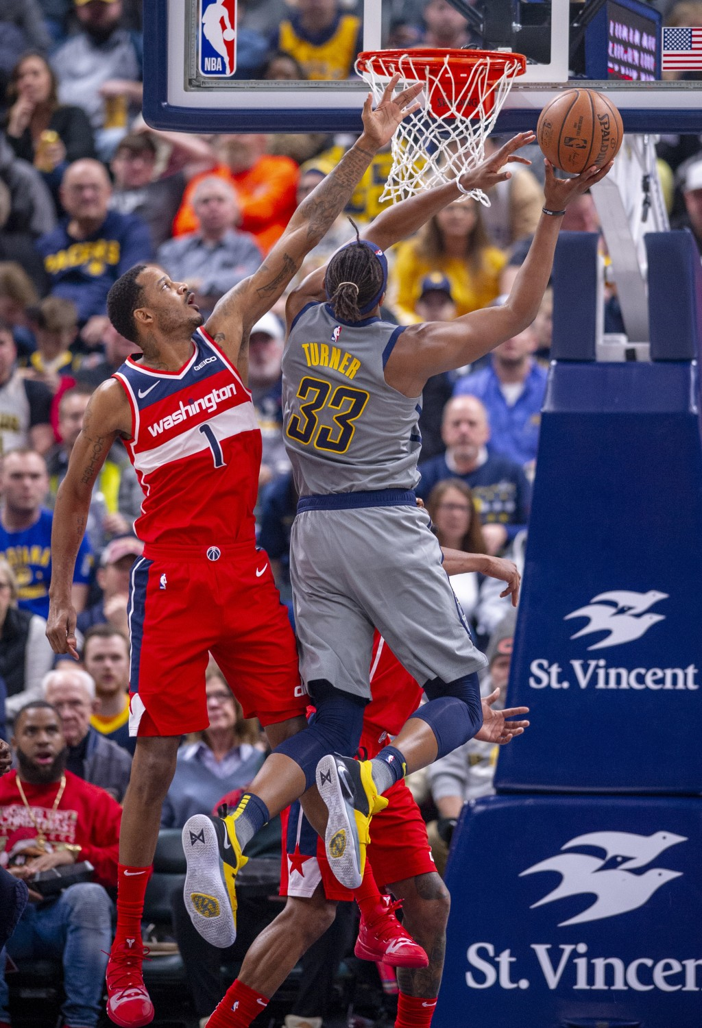 Indiana Pacers center Myles Turner (33) tries to shoot around the defensive efforts of Washington Wizards forward Trevor Ariza (1) during an NBA baske...