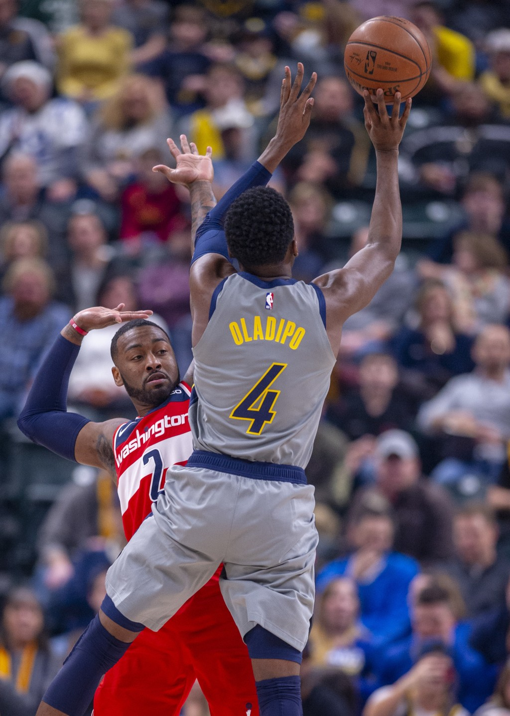 Indiana Pacers guard Victor Oladipo (4) collides with Washington Wizards guard John Wall (2) as he shoots during an NBA basketball game, Sunday, Dec.
