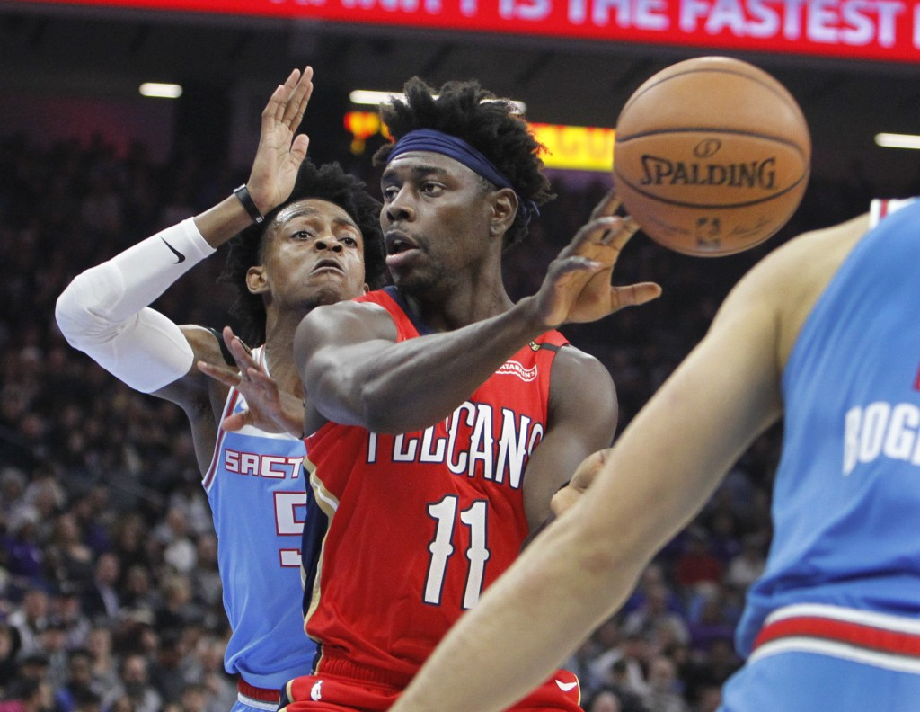 New Orleans Pelicans guard Jrue Holiday (11) passes the ball against Sacramento Kings guard De'Aaron Fox (5) during the first half of an NBA basketbal...