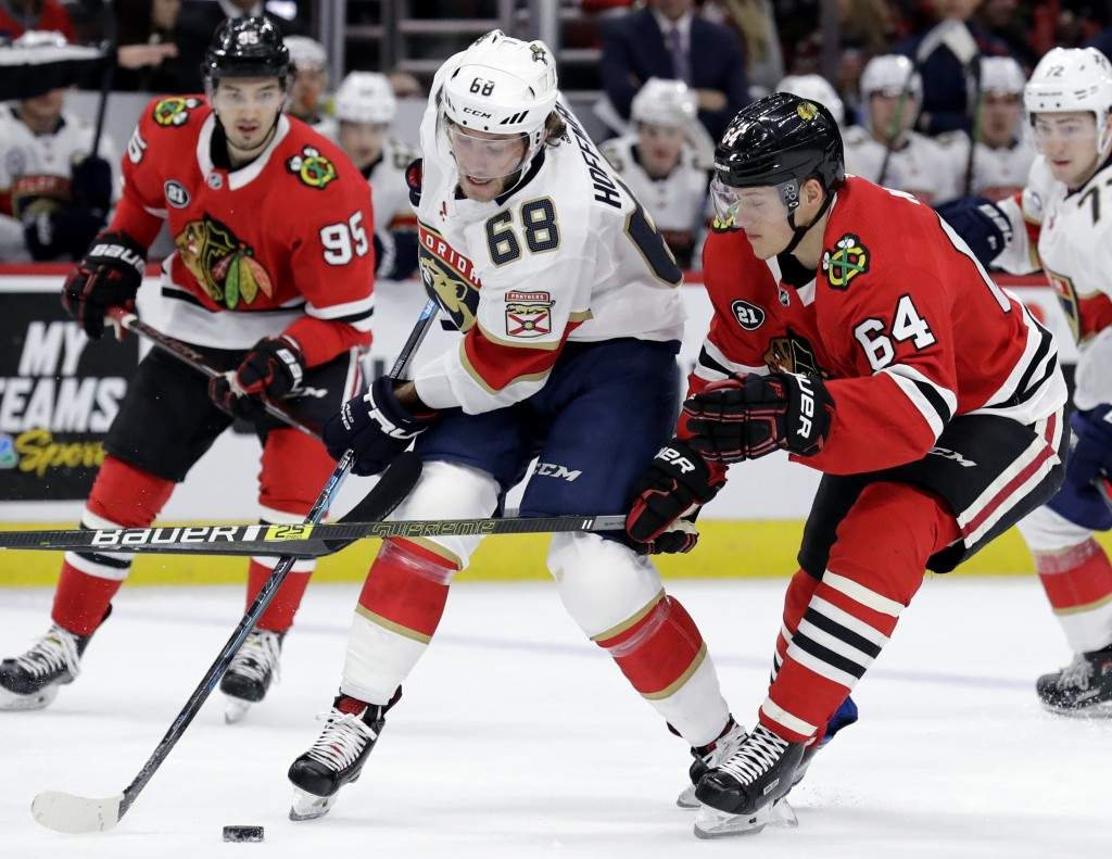Florida Panthers left wing Mike Hoffman (68) controls the puck against Chicago Blackhawks center David Kampf (64) during the second period of an NHL h...