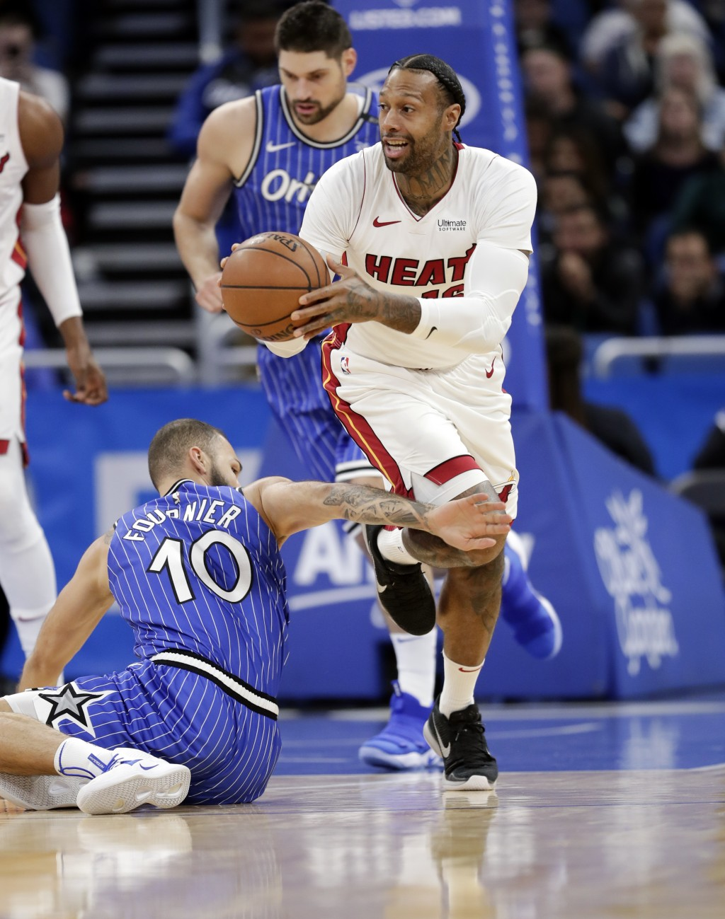 Miami Heat's James Johnson, right, moves past Orlando Magic's Evan Fournier (10) after scooping up a loose ball during the first half of an NBA basket...