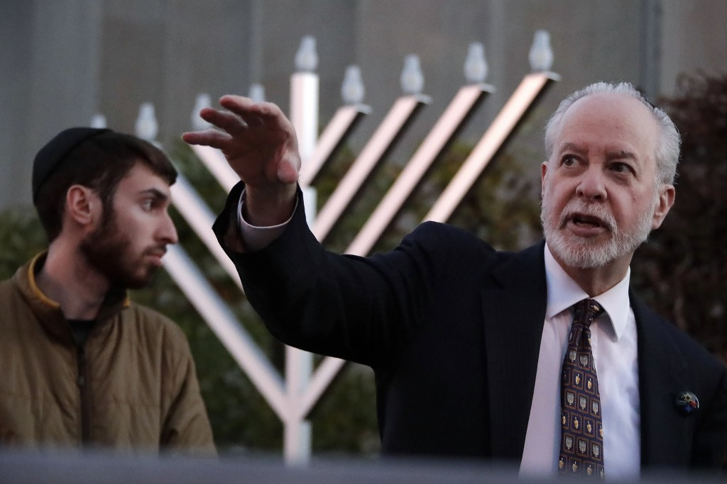 FILE - In this Dec. 2, 2018, file photo, Rabbi Jeffrey Myers, right and his son, Aaron, oversee the installation of a menorah outside the Tree of Life...