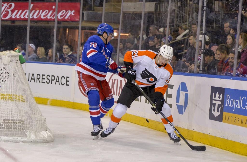 Philadelphia Flyers center Scott Laughton (21) battles New York Rangers defenseman Brady Skjei (76) for the puck during the first period of an NHL hoc
