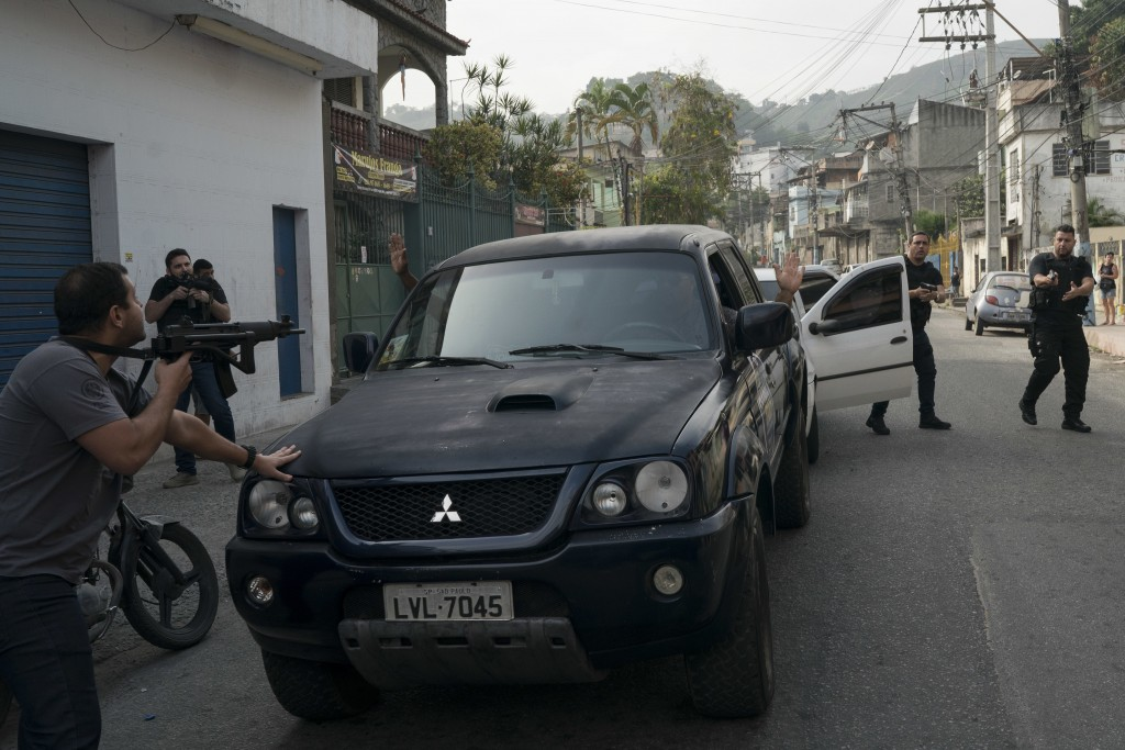 In this Sept. 3, 2018 photo, plain clothed police aim their weapons as they intercept a vehicle with three men inside who are suspected of being membe...