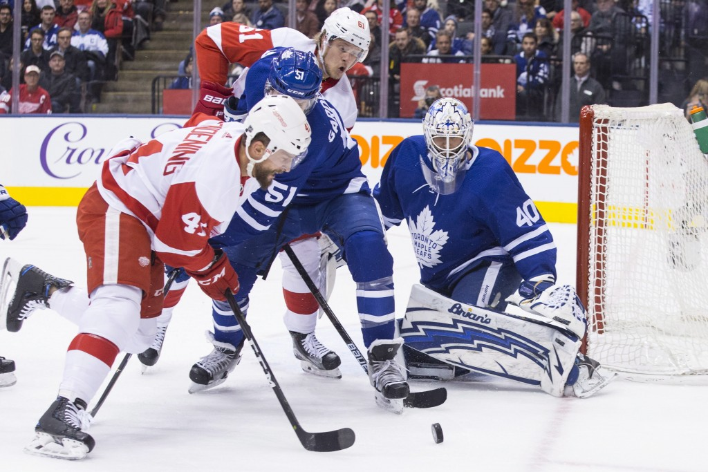 Detroit Red Wings Luke Glendening, left, goes after a loose puck in front of Toronto Maple Leafs goaltender Garret Sparks during first period NHL hock...