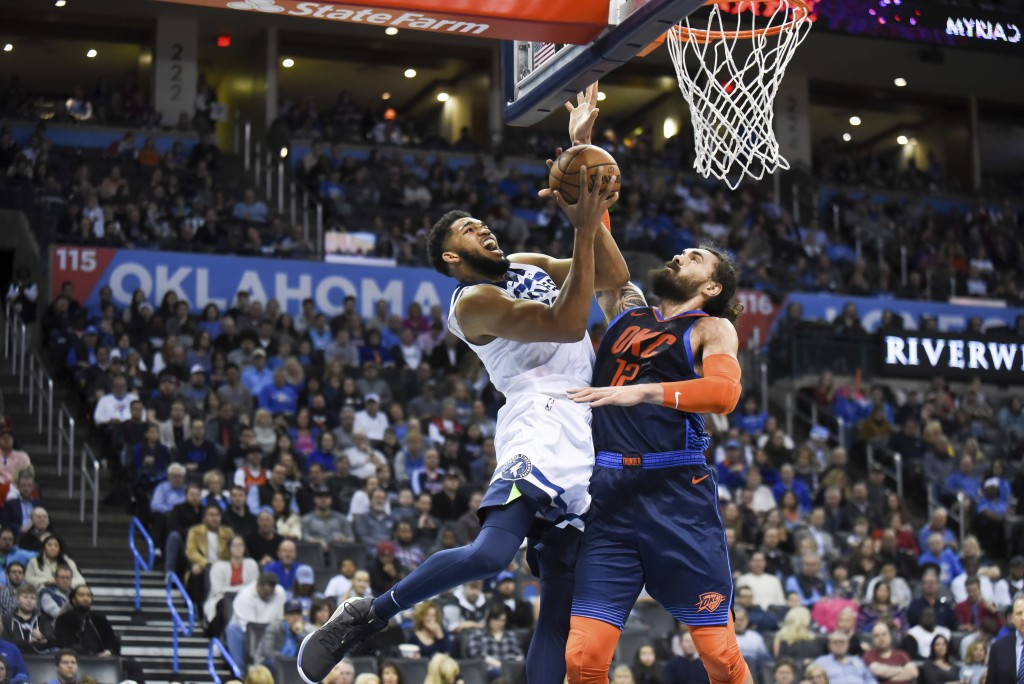 Minnesota Timberwolves center Karl-Anthony Towns, left, goes up to shoot over Oklahoma City Thunder center Steven Adams, right, in the first half of a...