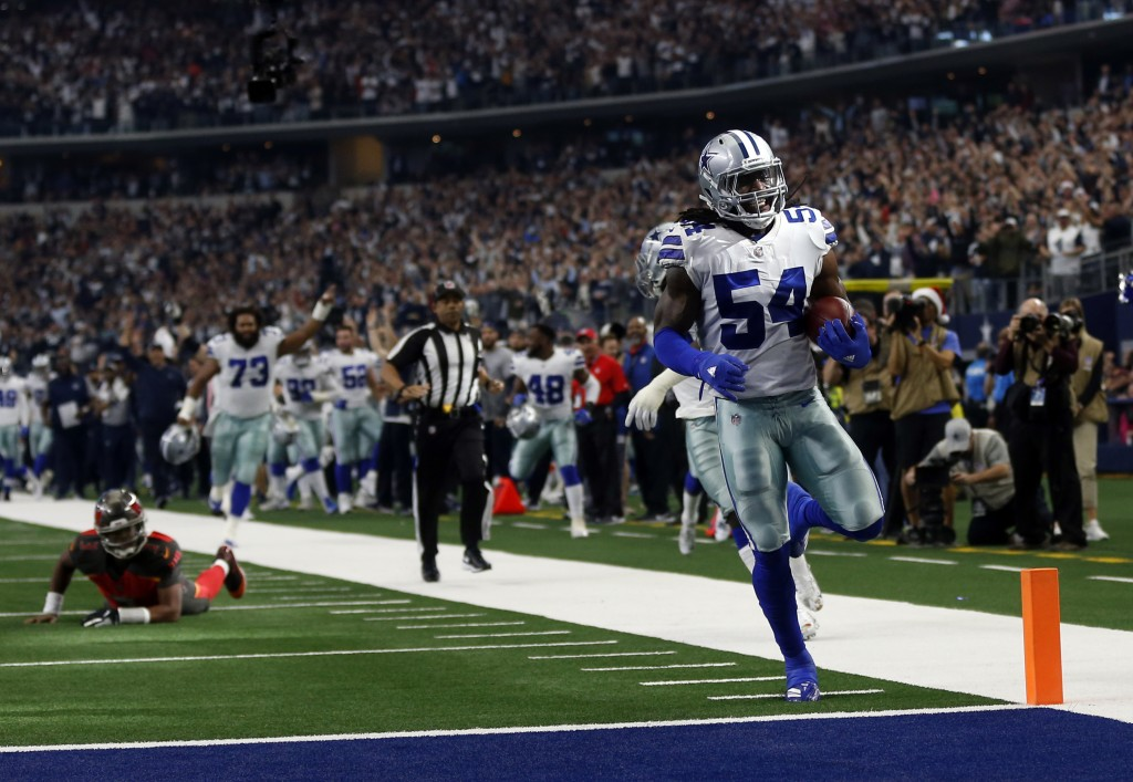 Tampa Bay Buccaneers quarterback Jameis Winston, left on field, looks on as Dallas Cowboys linebacker Jaylon Smith (54) scores a touchdown after recov...
