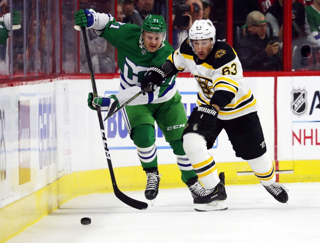 Boston Bruins' Brad Marchand (63) eyes the puck after battling Carolina Hurricanes' Lucas Wallmark (71) for position during the first period of an NHL...