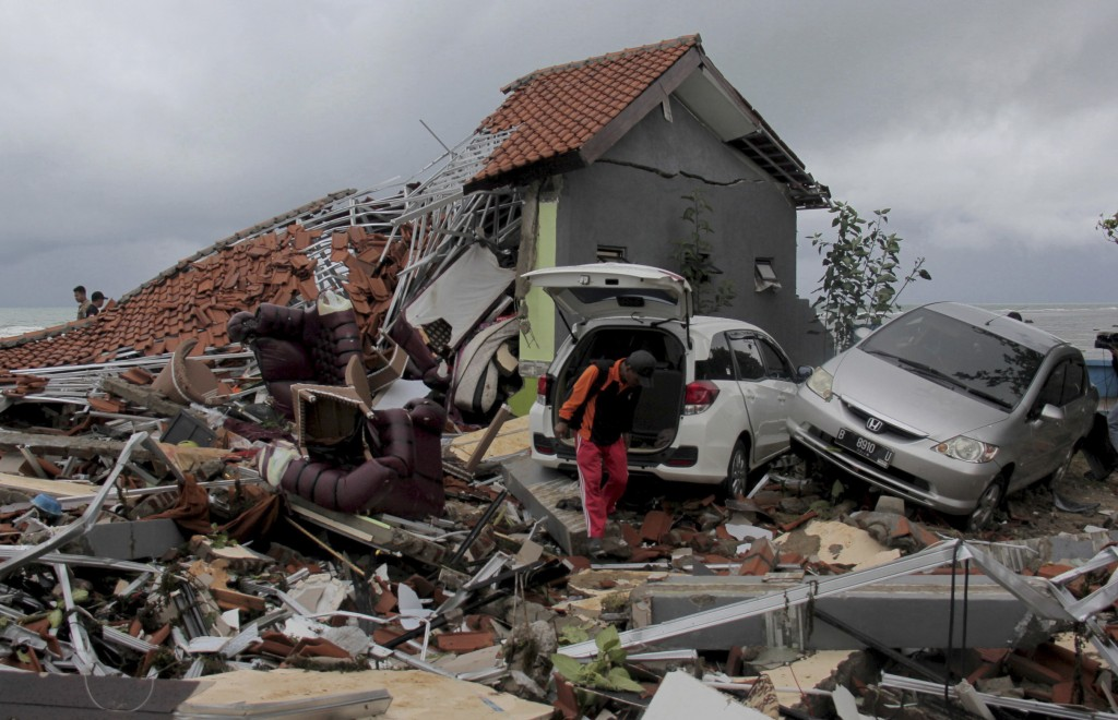 A man inspects the damage suffered by a building following a tsunami in Anyar, Indonesia, Sunday, Dec. 23, 2018. An eruption of one of the world's mos