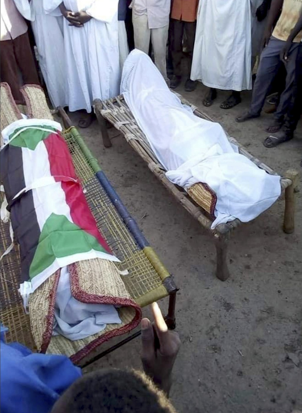 In this Friday Dec. 21, 2018 handout photo provided by a Sudanese activist, people pray in front of the bodies of 14-year old Mohammed Ismail and 10-y...