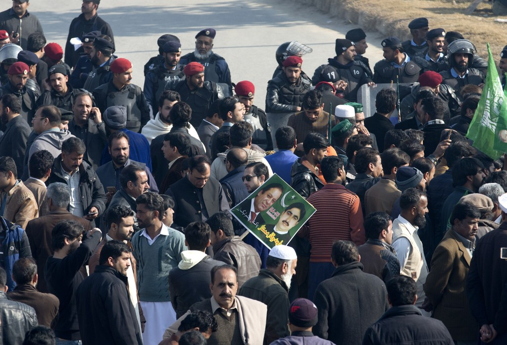 Police, rear, block supporters of former Pakistani Prime Minister Nawaz Sharif outside an accountability court in Islamabad, Pakistan, Monday, Dec. 24...