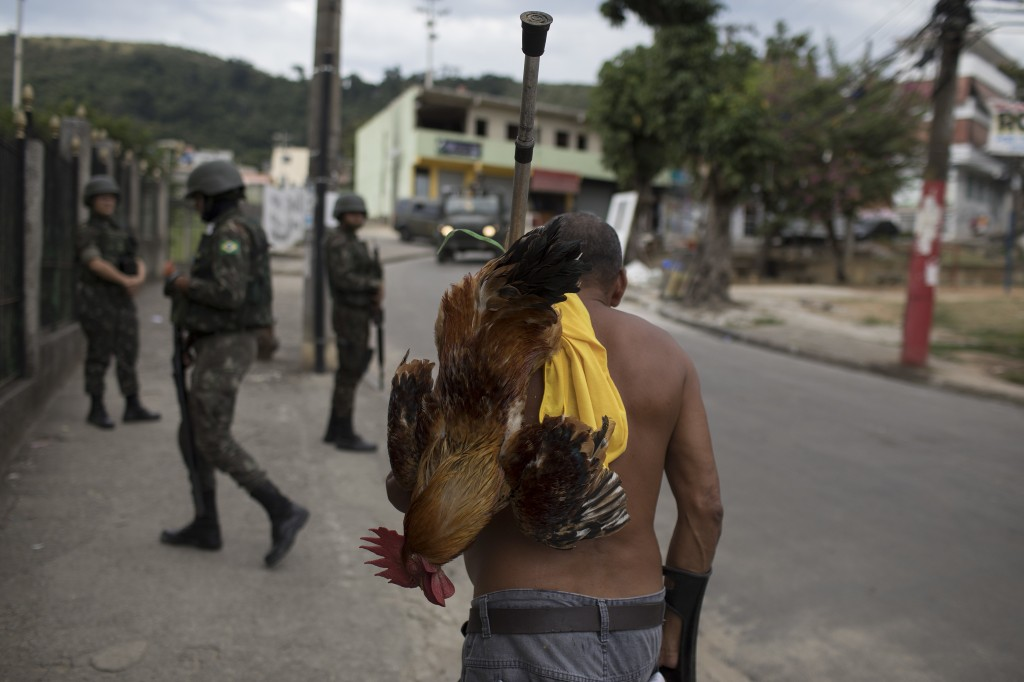 In this May 19, 2018 photo, a man carries a rooster as walks on the sidewalk where soldiers stand guard in the Bateau Mouche slum of Rio de Janeiro, B...