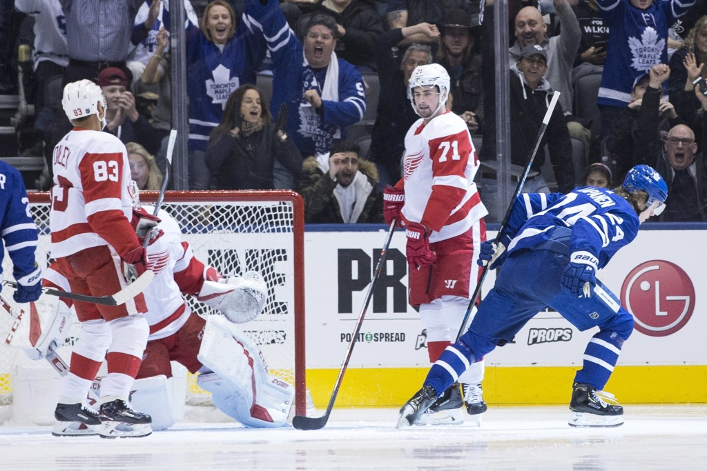 Toronto Maple Leafs right wing Kasperi Kapanen, right, turns after scoring his team's opening goal as Detroit Red Dylan Larkin (71) looks on during fi