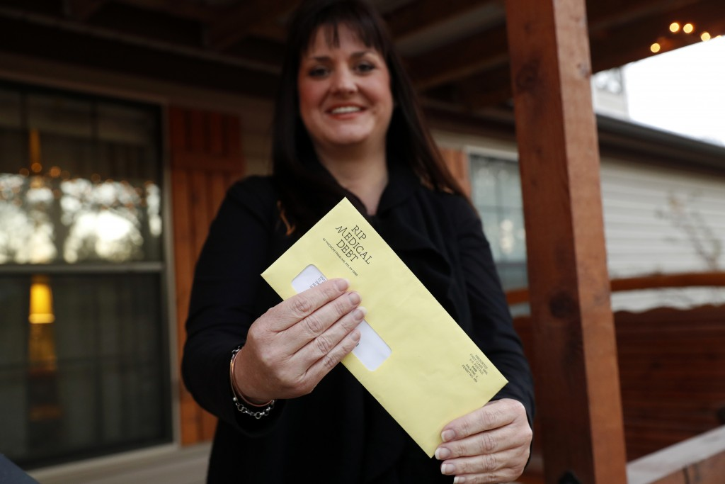 In this Dec. 20, 2018 photo, Reagen Adair holds on to an RIP Medical Debt yellow envelope as she poses for a photo at her home in Murchison, Texas. Th...