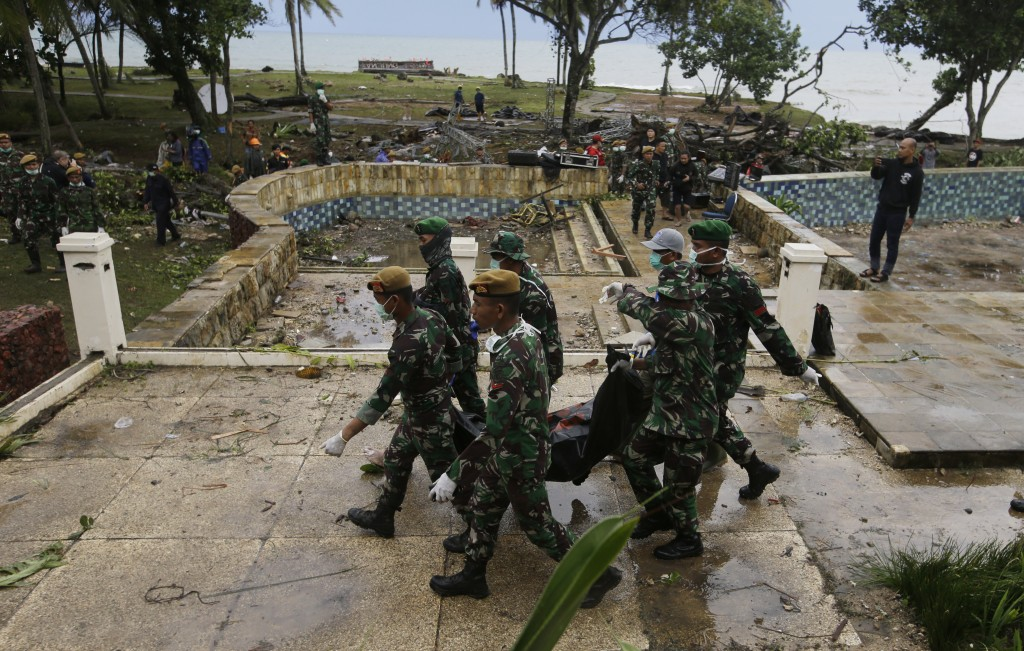 In this Monday, Dec. 24, 2018, photo, Indonesian soldiers carry the bodies of tsunami victims at a beach resort in Tanjung Lesung Indonesia. The tsuna...