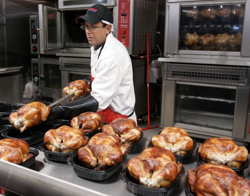 FILE - In this May 8, 2008, file photo, a butcher spreads out rotisserie-roasted chicken at Costco in Mountain View, Calif. There are shortcuts you ca...
