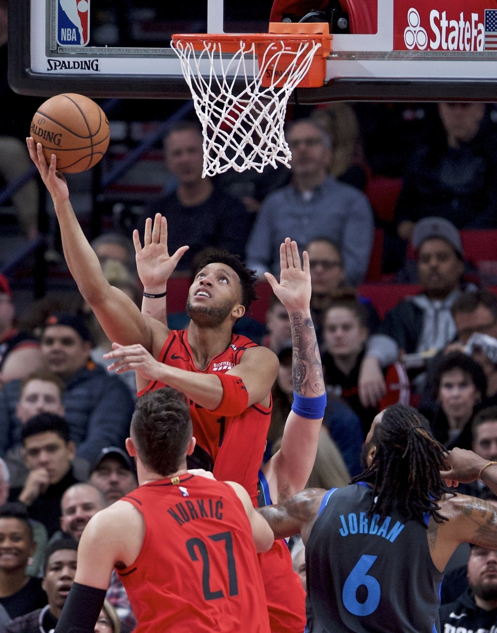 Portland Trail Blazers guard Evan Turner, left, shoots over Dallas Mavericks center DeAndre Jordan during the first half of an NBA basketball game in ...