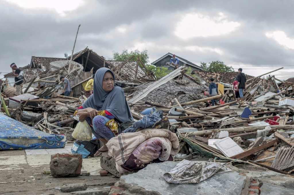 In this Monday, Dec. 24, 2018, photo, a tsunami survivor sits on a pice of debris as she salvages items from the location of her house in Sumur, Indon...