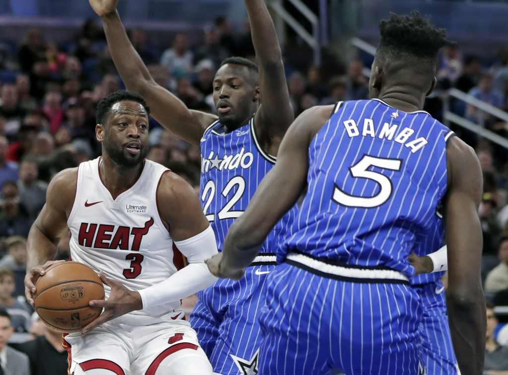 Miami Heat's Dwyane Wade (3) looks to pass the ball as he gets between Orlando Magic's Jerian Grant (22) and Mo Bamba (5) during the first half of an