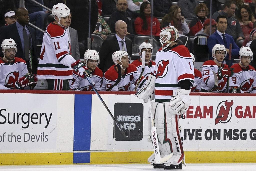 New Jersey Devils goaltender Keith Kinkaid (1) skates past the Devils' Brian Boyle (11) and head coach John Hynes, center (in suit), after being repla...