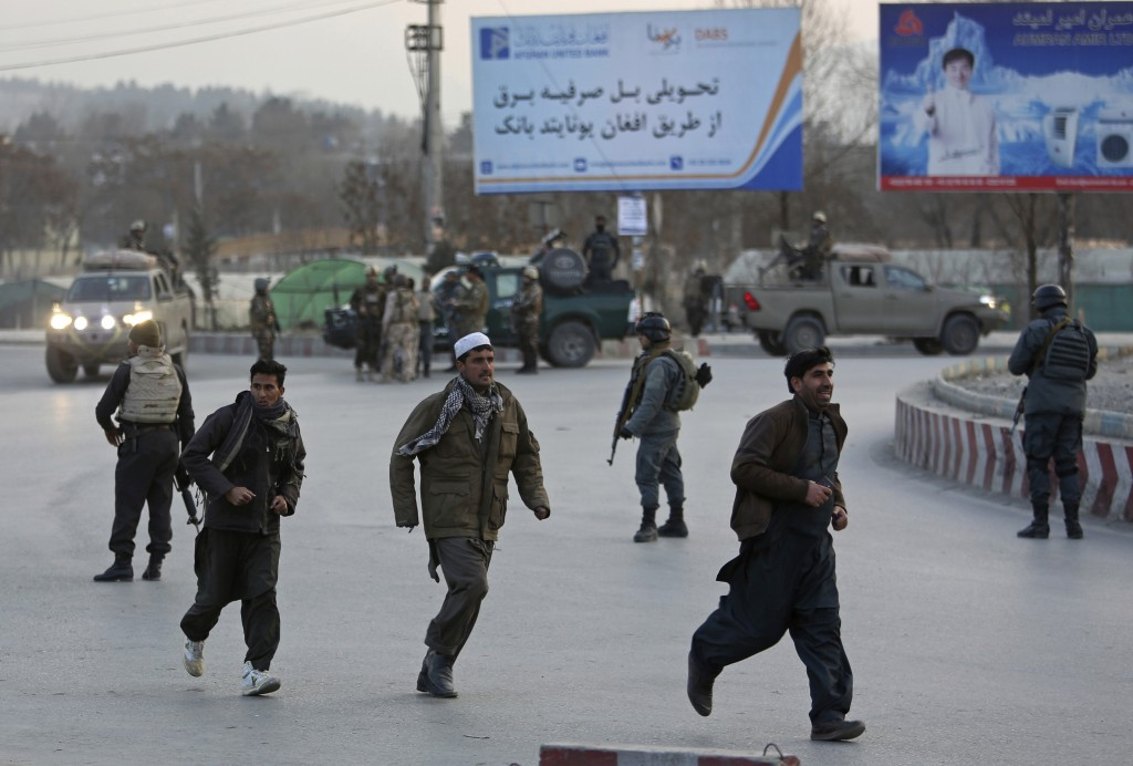 People run away from the site of a clash between insurgents and security forces in Kabul, Afghanistan, Monday, Dec. 24, 2018. Police have cordoned off...
