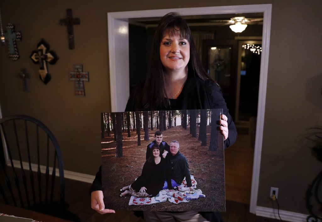 In this Thursday, Dec. 20, 2018 photo, Reagen Adair poses for a photo at her home holding a portrait of herself, with her husband Dale and son Mason, ...