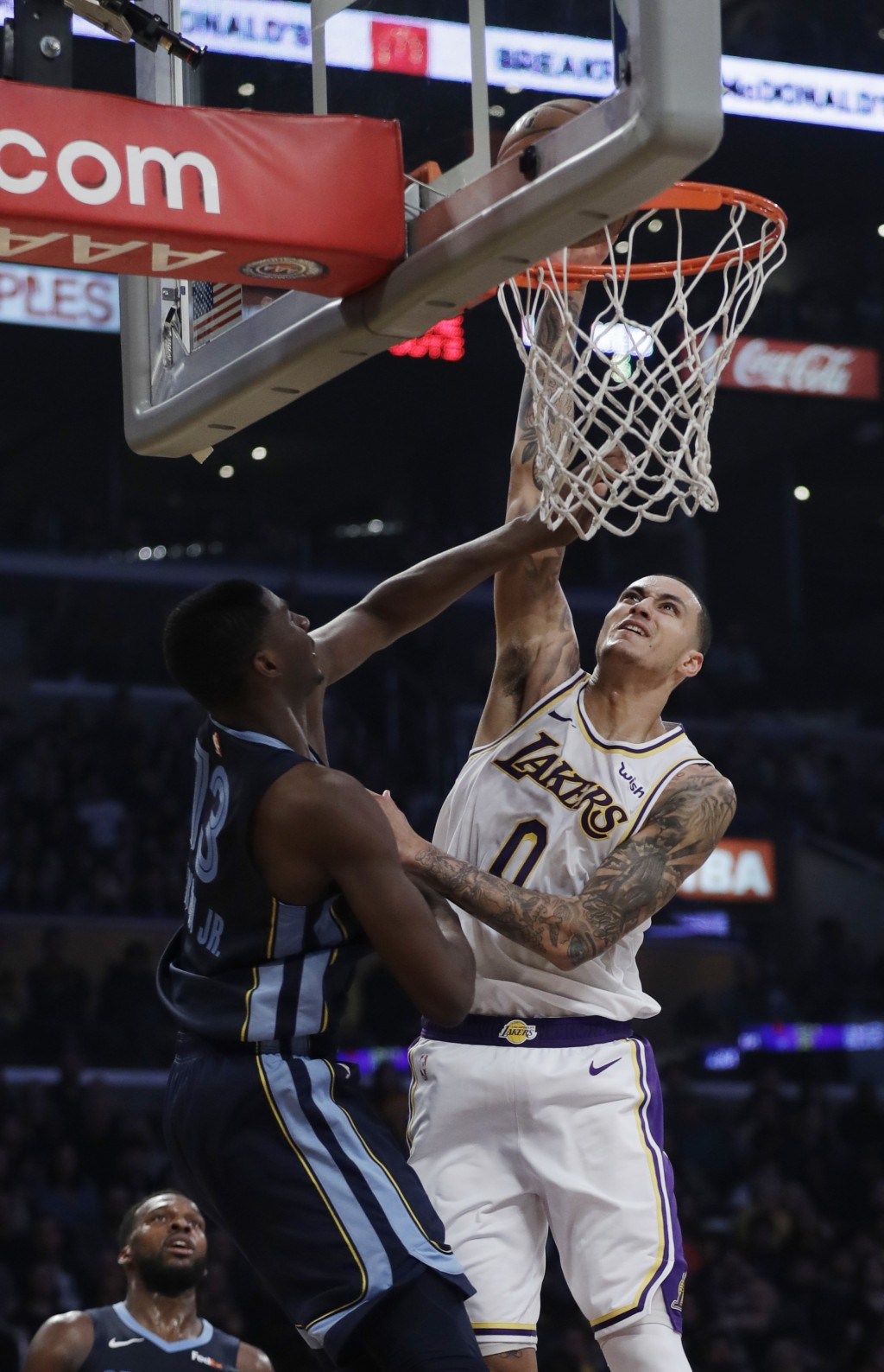 Los Angeles Lakers' Kyle Kuzma (0) goes up for a dunk as Memphis Grizzlies' Jaren Jackson Jr. defends during the first half of an NBA basketball game ...