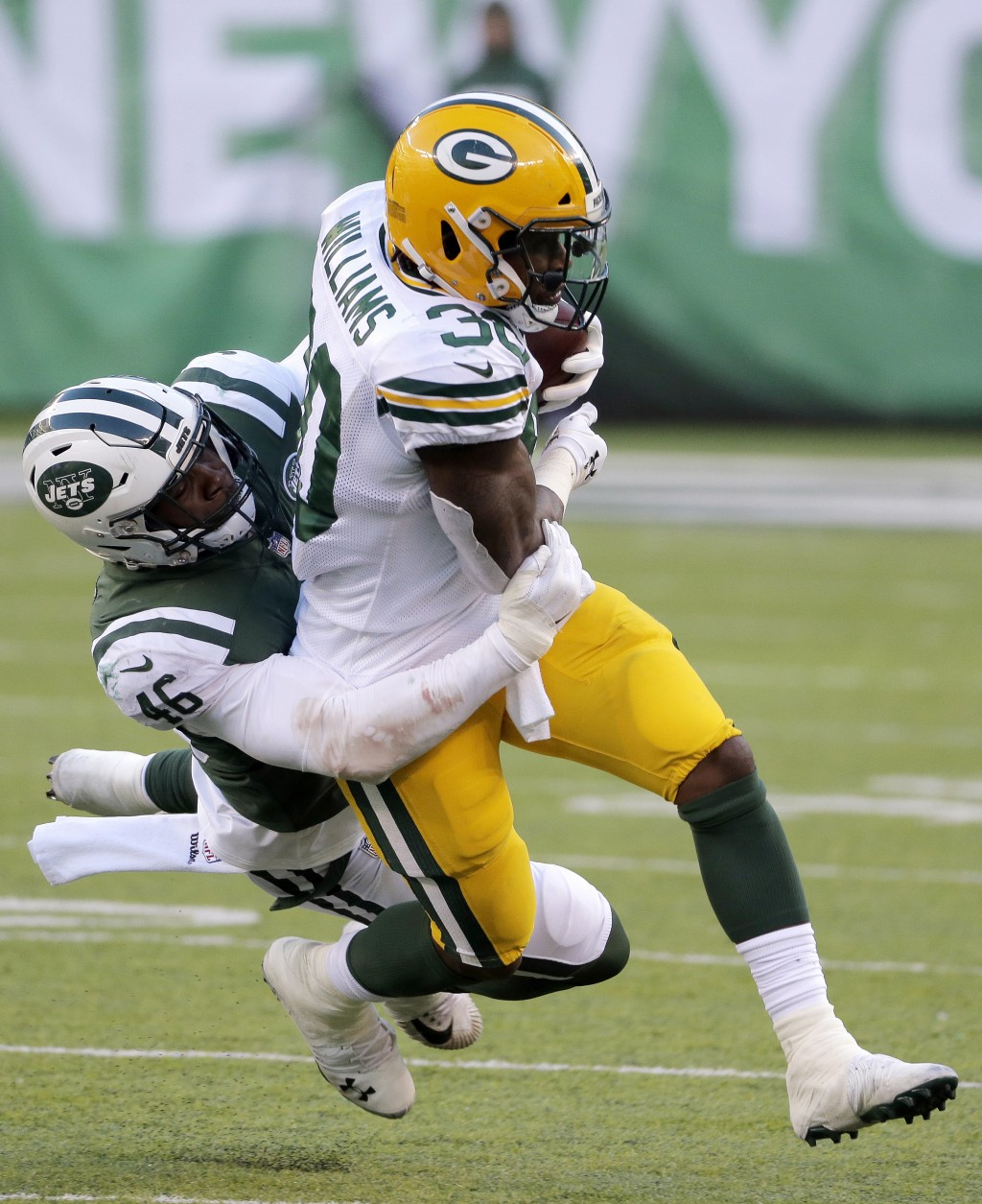 Green Bay Packers running back Jamaal Williams, right, is tackled by New York Jets linebacker Neville Hewitt during the second half of an NFL football...
