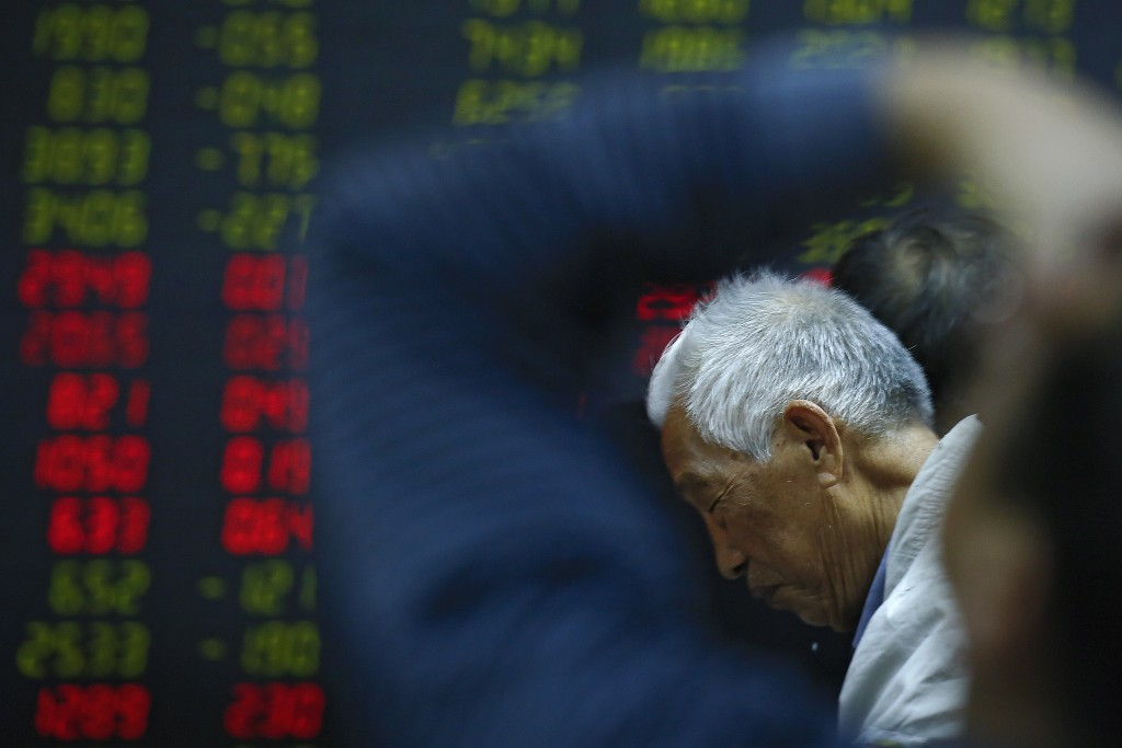 In this Oct. 24, 2018, photo, an investor reacts as he and investors monitor stock prices at a brokerage house in Beijing. Asian stocks were mostly lo...