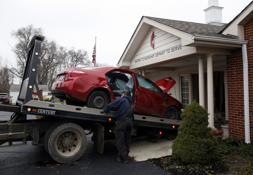 A car that crashed into the entrance of the Crossroads United Methodist Church is towed out of the doorway on Sunday, December 23, 2018 in Columbus, O...