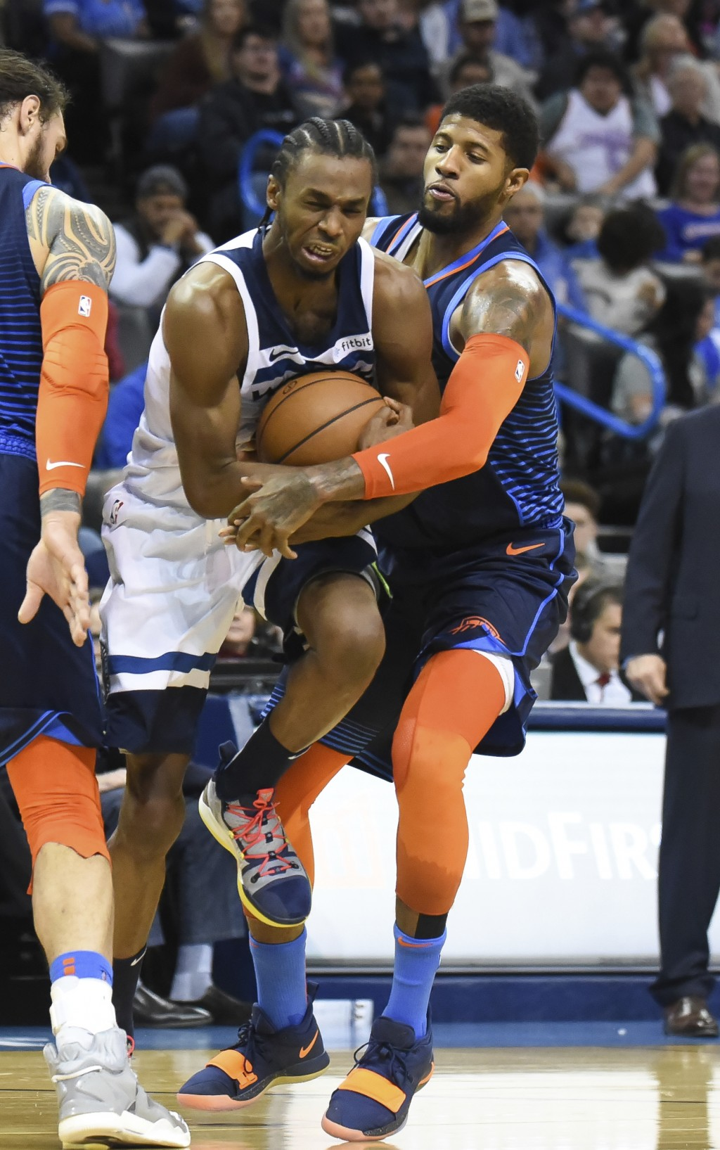 Oklahoma City Thunder forward Paul George, right, tries to get the ball away from Minnesota Timberwolves guard Andrew Wiggins, left, in the first half...