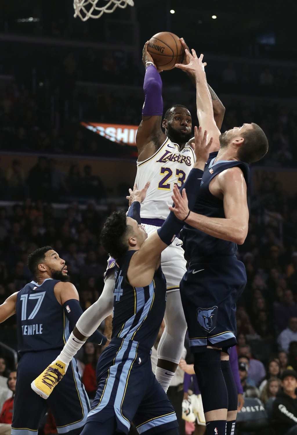 Los Angeles Lakers' LeBron James (23) passes as Memphis Grizzlies' Marc Gasol, right, and Dillon Brooks, bottom center, defend during the first half o...