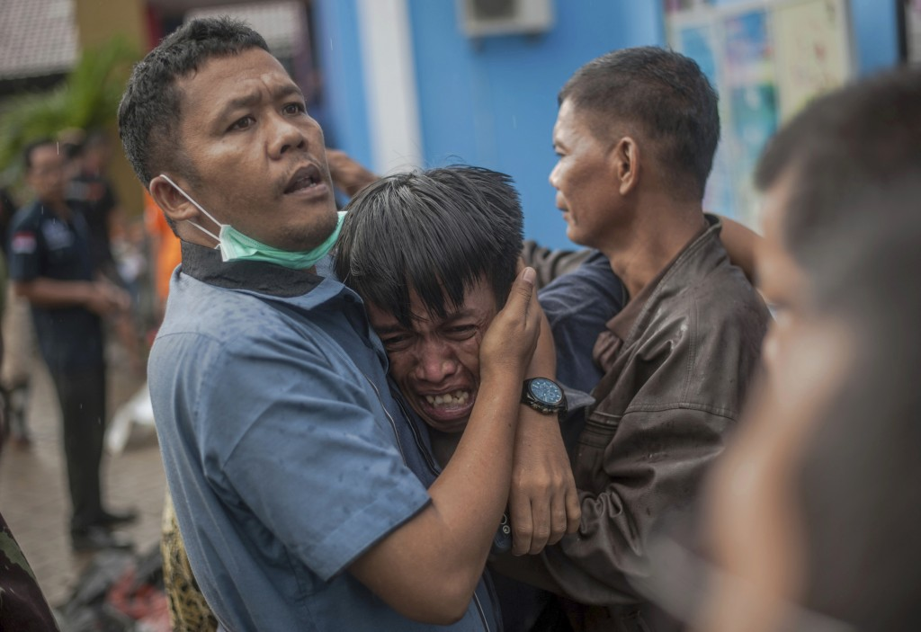 In this Sunday, Dec. 23, 2018, file photo, a man reacts after identifying his relative among the bodies of tsunami victims in Carita, Indonesia. The t...
