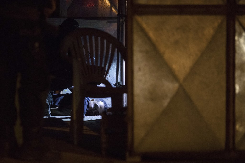 In this Aug. 31, 2018 photo, the bloodied body of a man lays on the floor of a kiosk, as forensic police use a flashlight to inspect the crime scene i...