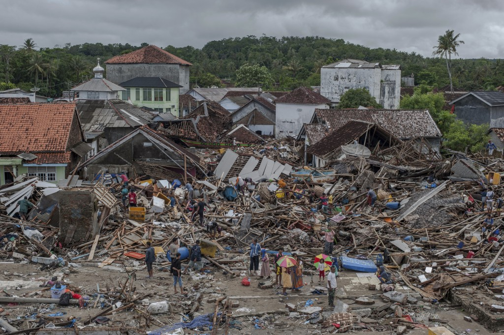 In this Monday, Dec. 24, 2018, file photo, people inspect the damage at a tsunami-ravaged village in Sumur, Indonesia. Doctors are working to help sur...