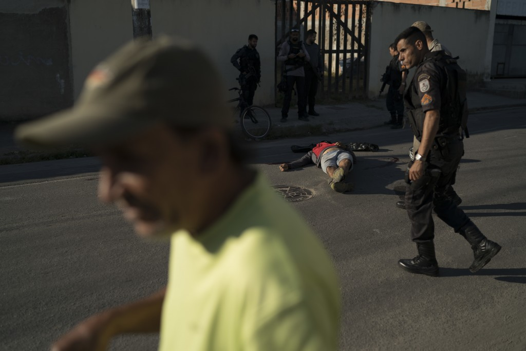 In this Sept. 1, 2018 photo, the body of a motorcycle taxi driver lies on the street after he was shot dead, as police and pedestrians move about in S...