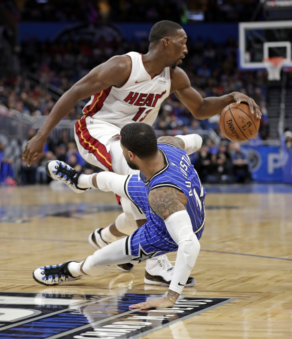 Orlando Magic's D.J. Augustin, right, tumbles backward as he collides with Miami Heat's Bam Adebayo during the first half of an NBA basketball game, S...