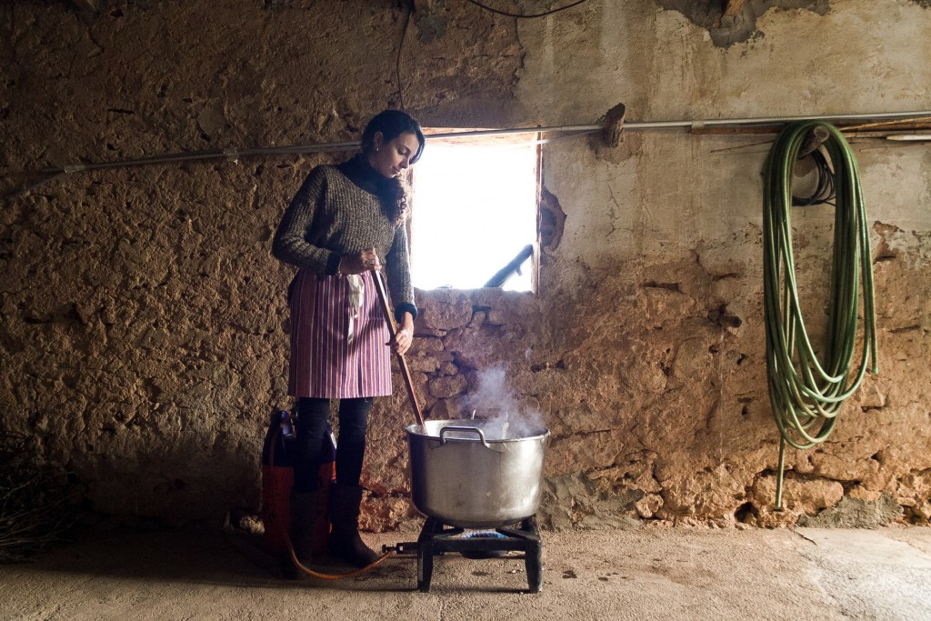 In this photo taken on Nov. 24, 2018, Laura, one of the women who has come to help with the slaughter, stirs the fat of the boiling pork for butter pr...