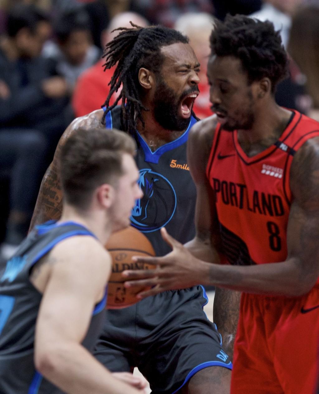 Dallas Mavericks center DeAndre Jordan, back left, reacts after scoring over Portland Trail Blazers forward Al-Farouq Aminu during the first half of a...