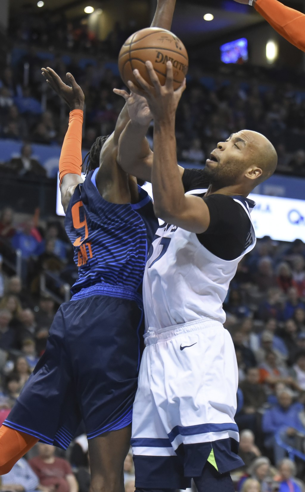 Minnesota Timberwolves forward Taj Gibson, right, goes up for a shot past Oklahoma City Thunder forward Jerami Grant, left, in the first half of an NB...