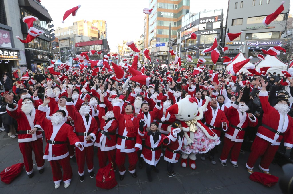 In this Monday, Dec. 24, 2018, file photo, volunteers clad in Santa Claus costumes throw their hats in the air as they gather to deliver gifts for the...