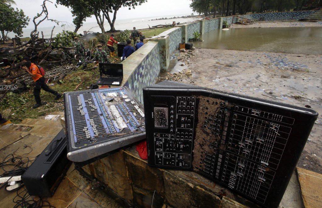 A rescue team walks near an audio mixer damaged by a tsunami at Tanjung Lesung beach resorts Indonesia, Monday, Dec. 24, 2018. The tsunami that roared...