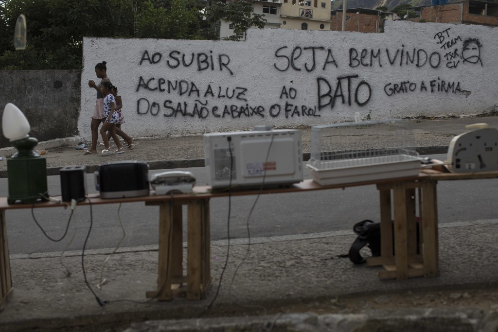 """In this May 19, 2018 photo, residents walk past used items for sale and a wall covered by a Portuguese message from drug traffickers: """"Welcome to Bato..."""