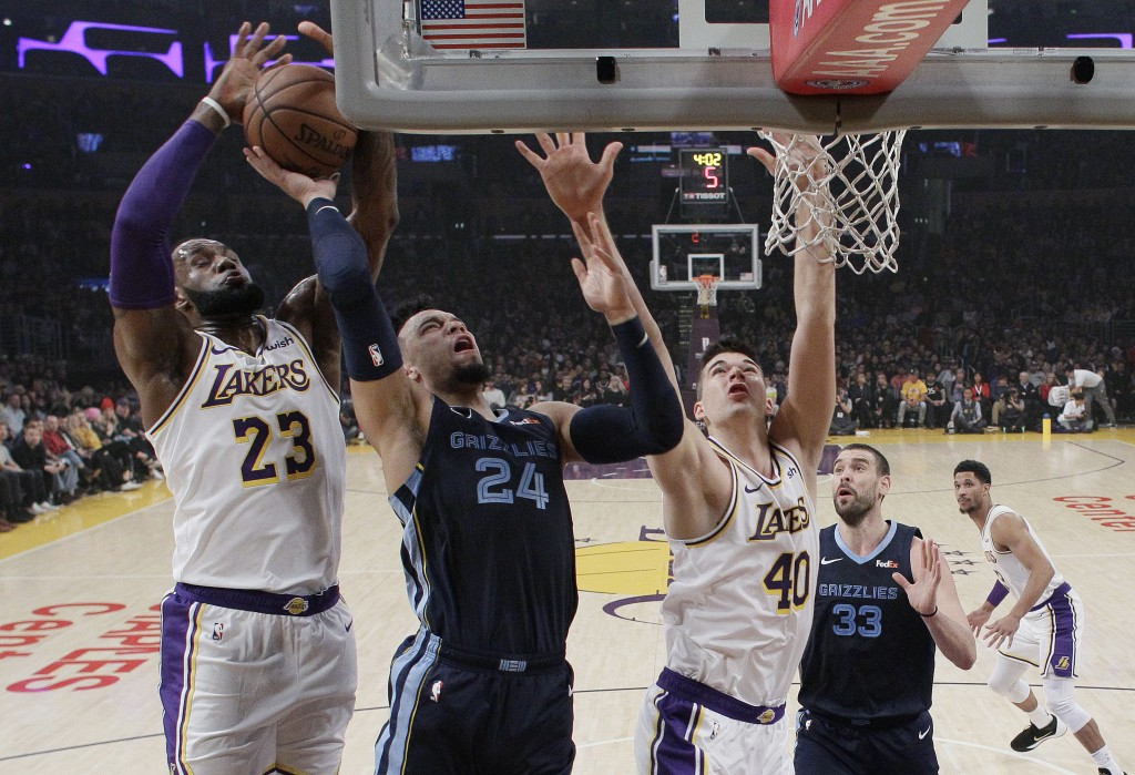 Memphis Grizzlies' Dillon Brooks (24) drives to the basket as Los Angeles Lakers' LeBron James (23) and Ivica Zubac (40) defend during the first half ...