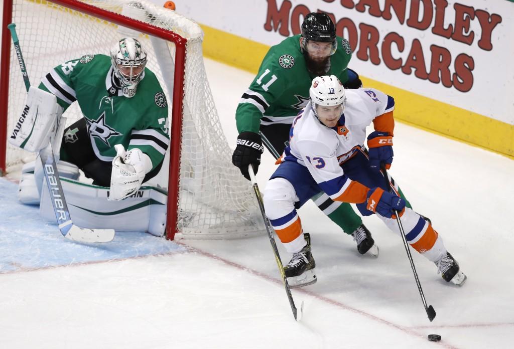 New York Islanders center Mathew Barzal (13) skates with the puck against Dallas Stars center Martin Hanzal (11) and goaltender Anton Khudobin (35) du...
