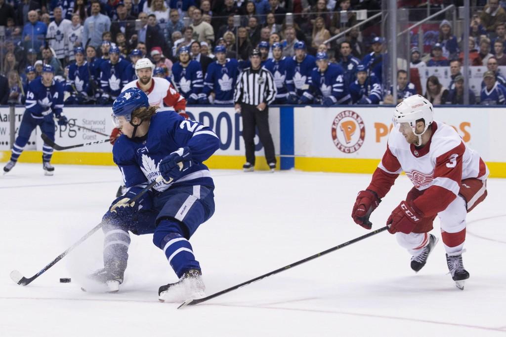 Toronto Maple Leafs Kasperi Kapanen, left, turns on Detroit Red Wings Nick Jensen before scoring the game-winning goal in overtime during NHL hockey a...